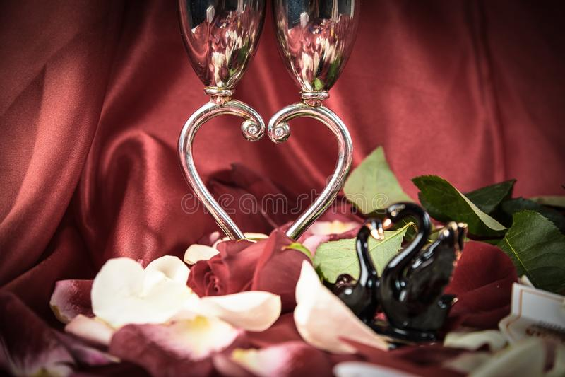 Wedding wine glasses and a pair of black swans on a festive background. royalty free stock photos