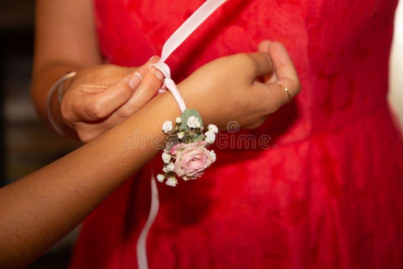 Wedding witness puts on her bride flower bracelet. A wedding witness puts on her bride flower bracelet stock photos
