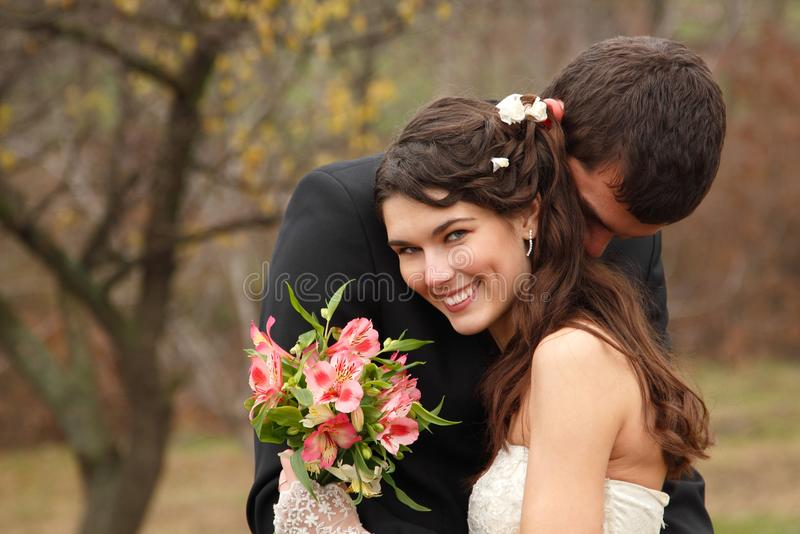 Wedding, young groom kiss bride in love over autumn nature backg. Round, park fall outdoor royalty free stock photos