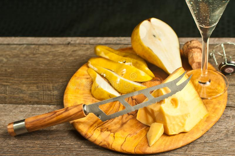 Wedge of cheese, cheese knife, and pear as pairings for a french wine tasting event. Top, front view, close distance of a wedge of cheese, cheese knife, sliced stock photography
