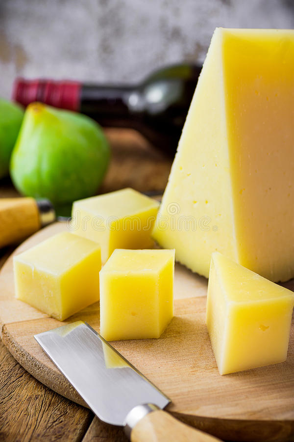 Wedge of Spanish cured hard goat cheese cut in cubes on wood platter. Ripe green figs. Knife and fork, bottle of wine on table. royalty free stock photography