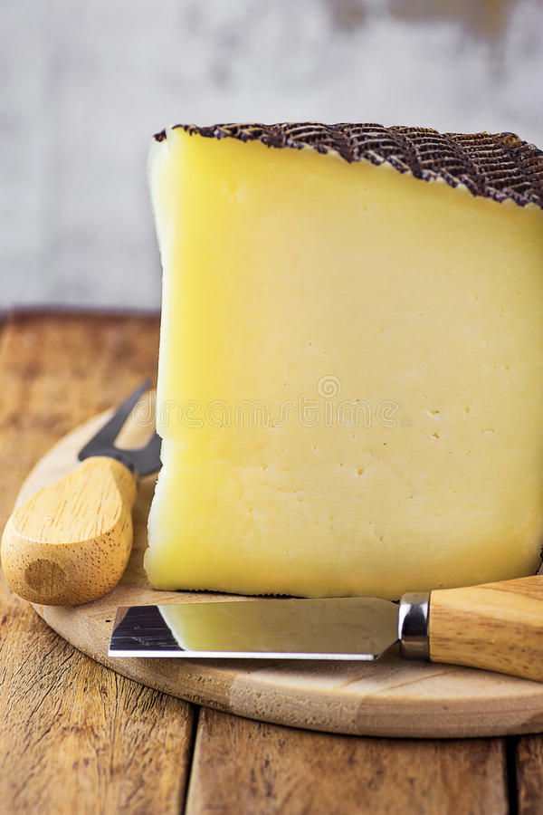 Wedge of Spanish goat cow and ewe cheese with black textured rind on wood cutting board. Special fork and knife. Rustic kitchen in royalty free stock images