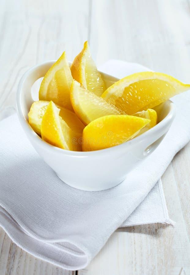 Wedges of Fresh Lemon in White Bowl on Table royalty free stock photo