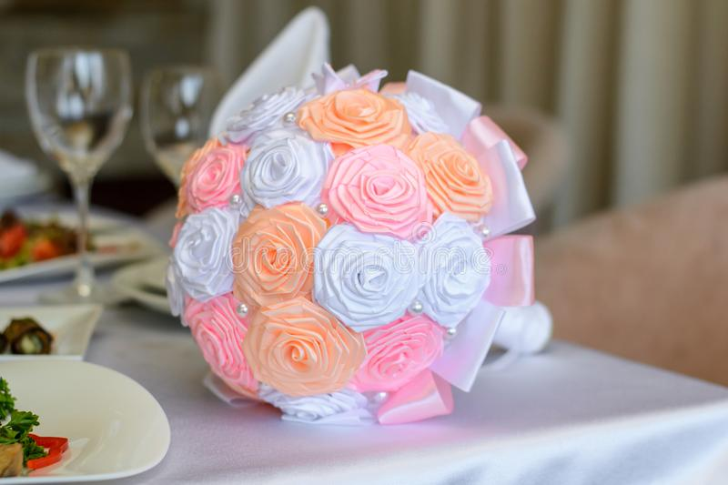 Weding bouquet on a table. Close up photo of beautiful ideal perfect charming orange white and pink silk fabric small wedding brid stock photography
