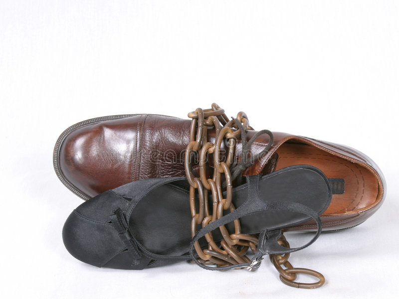 WedLOCK. Man and woman dress shoes bound together with bronze chain stock images