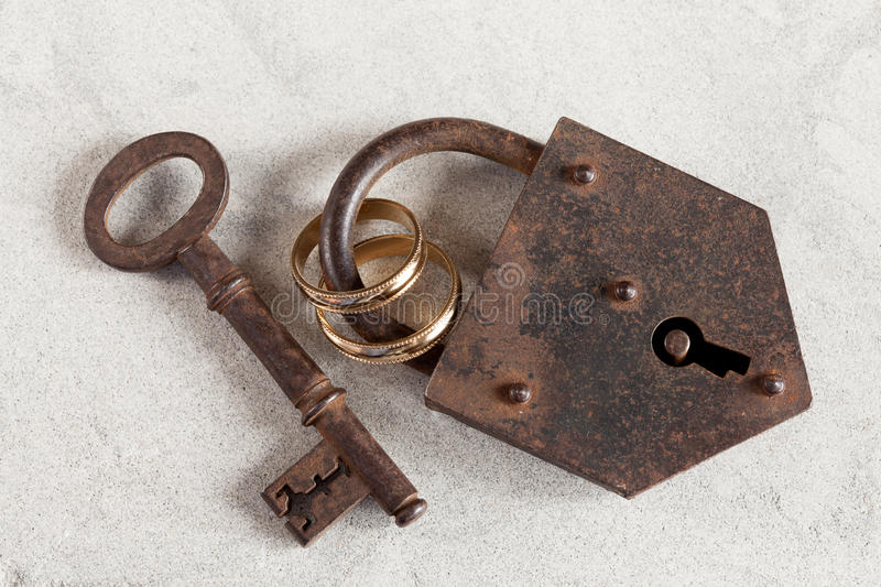 Wedlock. Wedding rings boud by a rusty old padlock royalty free stock image
