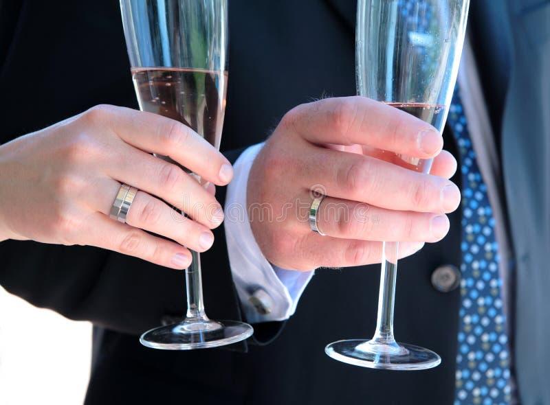 Weds recentemente as mãos com anéis de casamento e champanhe foto de stock royalty free
