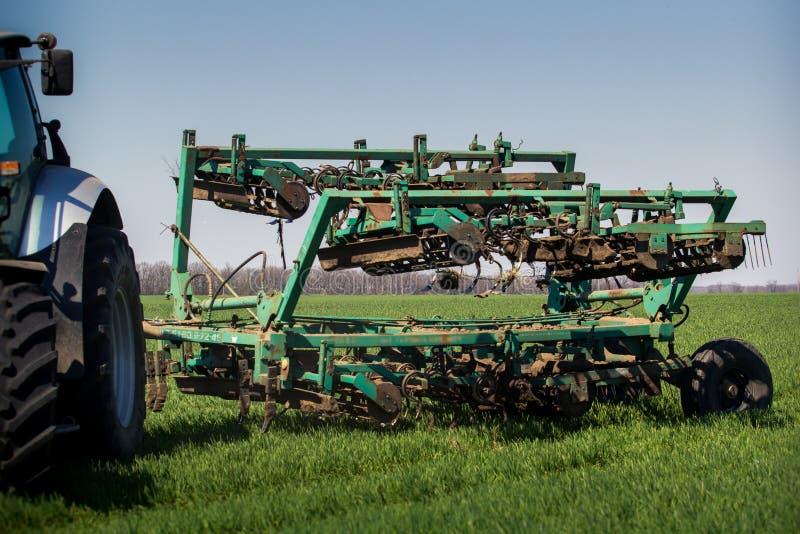 weeding-máquina detrás del tractor en campo de trigo verde fotos de archivo libres de regalías