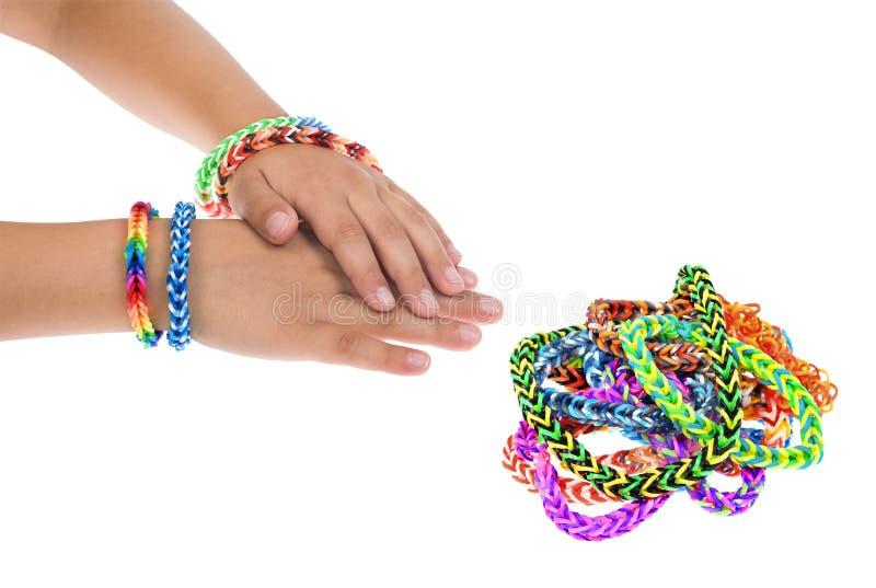 Weefgetouw rubberarmbanden op de handen van een jong kind stock foto's