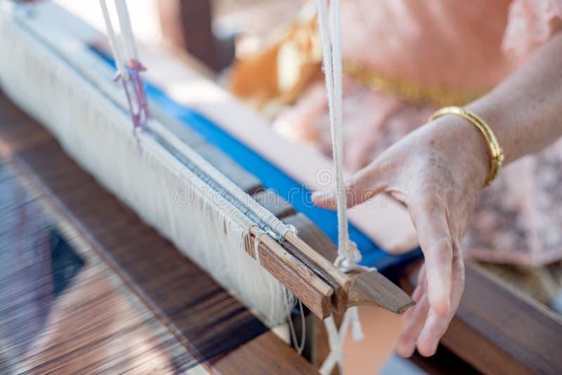weefselkatoen op het hand houten weefgetouw in Aziatische traditionele cultur royalty-vrije stock afbeeldingen