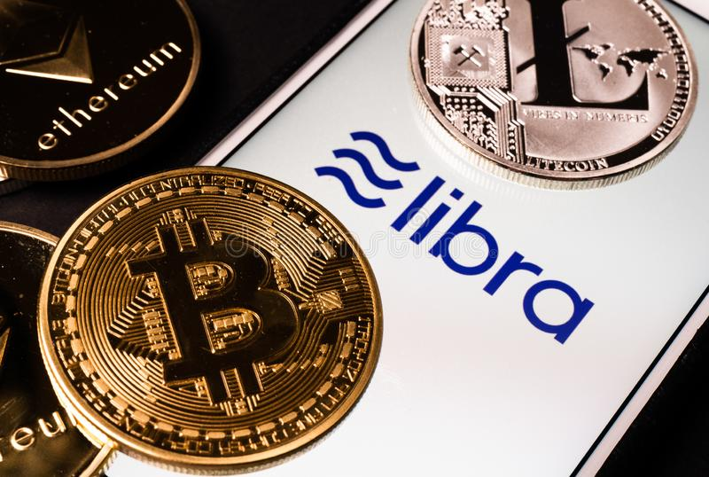 Weegschaal het Facebook-cryptocurrencyembleem op het mobiele telefoonscherm en echte muntstukken van andere crypto zoals Bitcoin  stock afbeelding