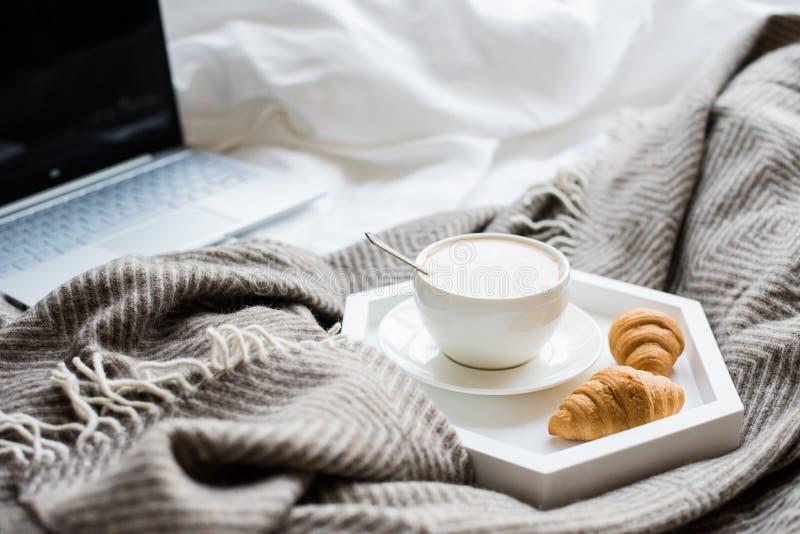 Week-end confortable à la maison, ordinateur portable et café dans le lit photos libres de droits
