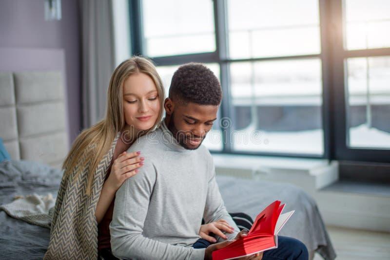 Week-end interracial heureux de dépense de couples ensemble à la maison, détendant avec le livre images stock