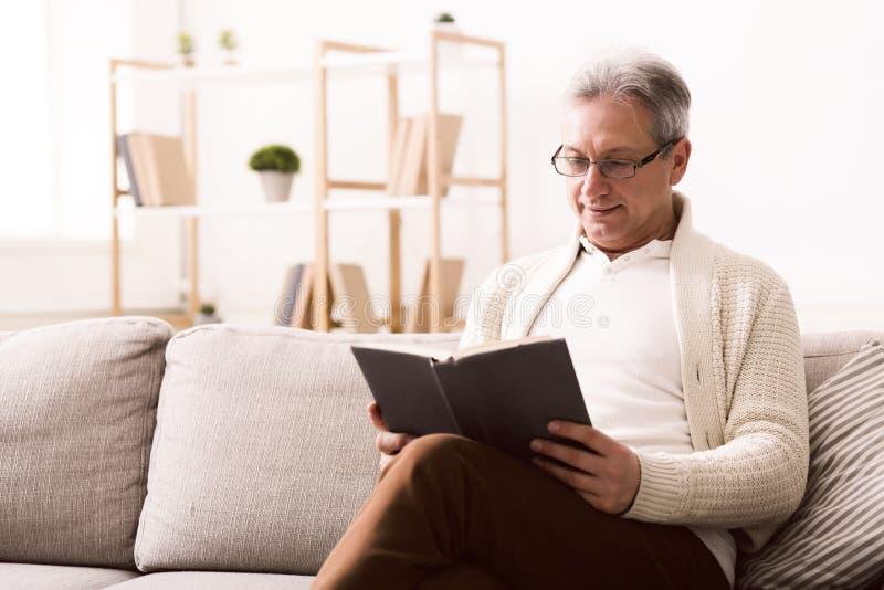 Week-ends heureux Livre de lecture de retraité sur le sofa photographie stock libre de droits