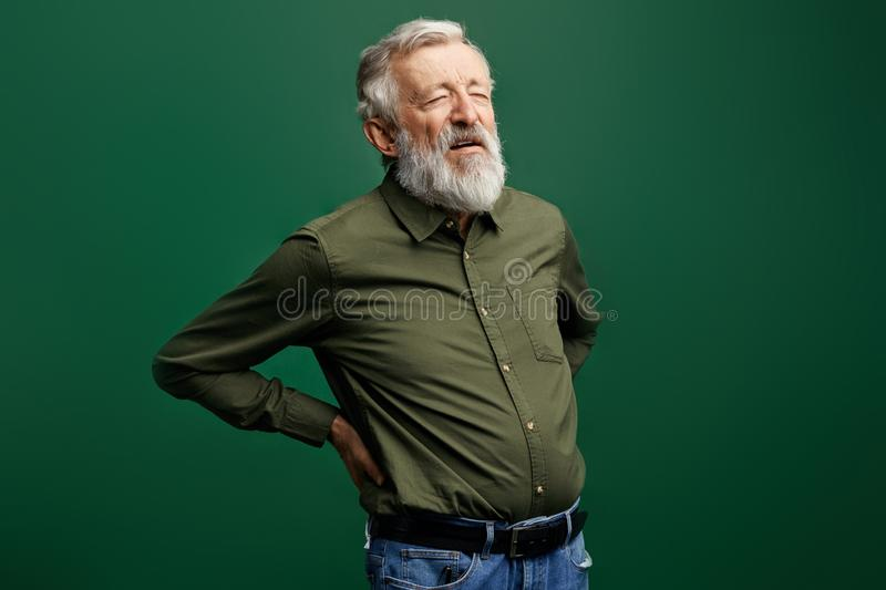 Week sick old man cannot stand stright, poor man suffering from radiculitis royalty free stock photo