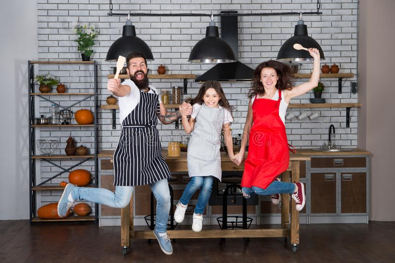 Weekend breakfast. Cooking with child might be fun. Having fun in kitchen. Family mom dad and little daughter wear. Aprons jump in kitchen. Family having fun royalty free stock photo