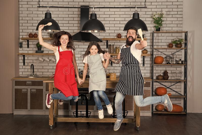 Weekend breakfast. Cooking with child might be fun. Having fun in kitchen. Family mom dad and little daughter wear. Aprons jump in kitchen. Family having fun royalty free stock image