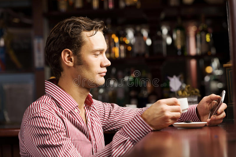 Weekend evening. Young handsome man in casual sitting at bar and talking on phone stock images