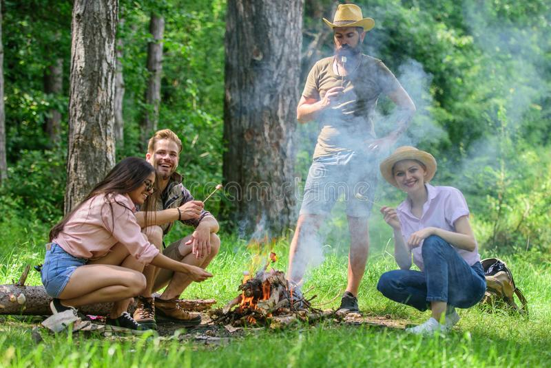 Weekend in forest benefits. Roasting marshmallows popular group activity around bonfire. Youth at picnic roasting royalty free stock photos