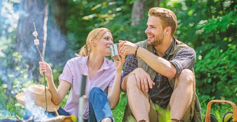 Weekend picnic. Food for hike and camping. Couple sit near bonfire eat snacks and drink. Couple take break to eat nature. Background. Couple in love camping stock photo