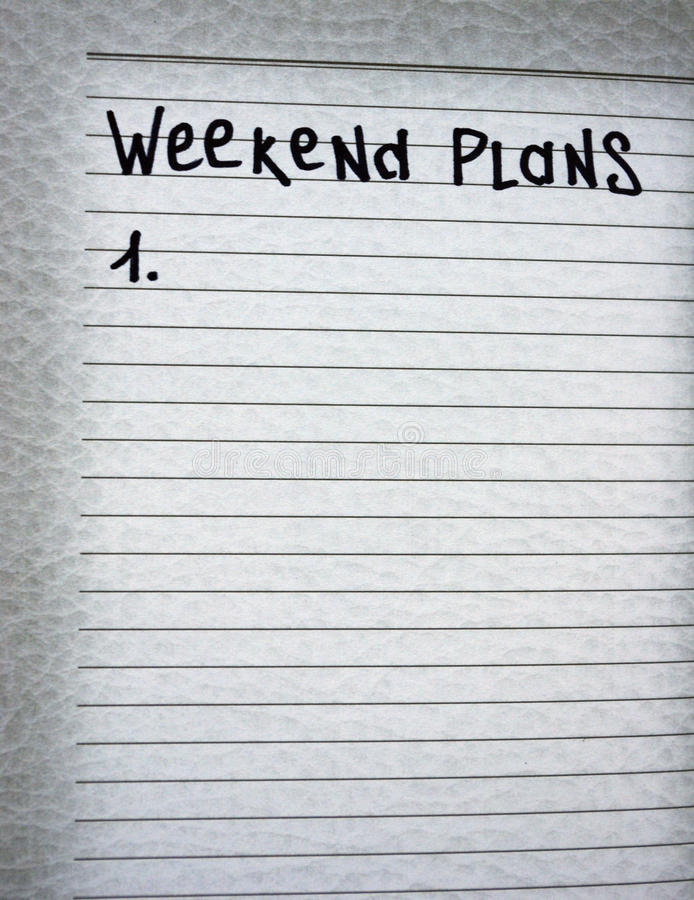 Weekend plans. Writing in his notebook plans for the weekend royalty free stock image