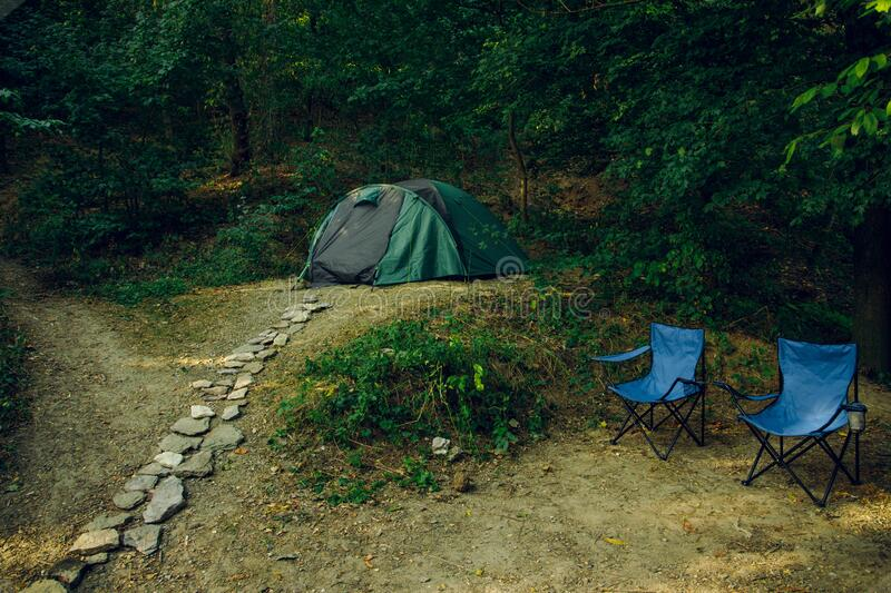 Weekend relaxation camp site tent two chairs without people here in forest edge nature outside environment life style concept. Picture royalty free stock images