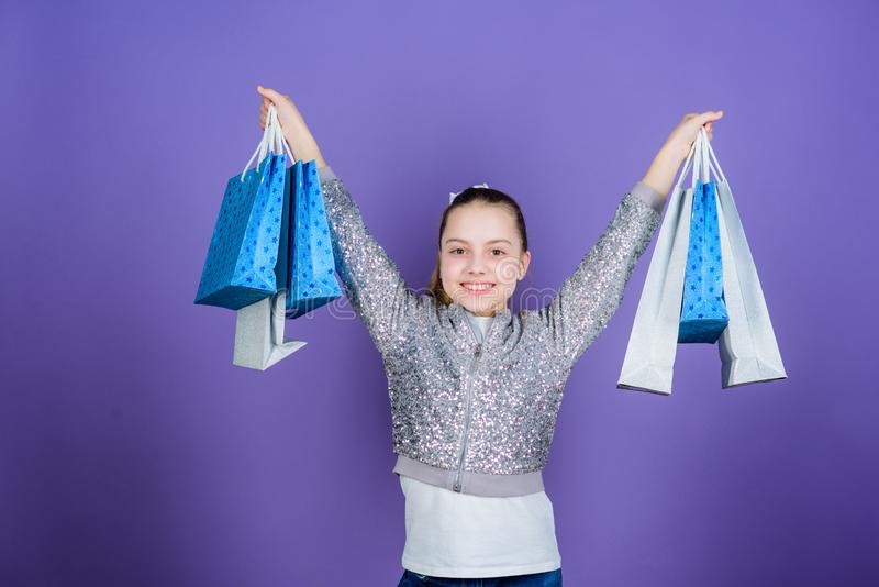 Weekend sale. Happy child. Little girl with gifts. Small girl with shopping bags. Kid fashion. shop assistant with. Package. Sales discounts. special offer stock photography
