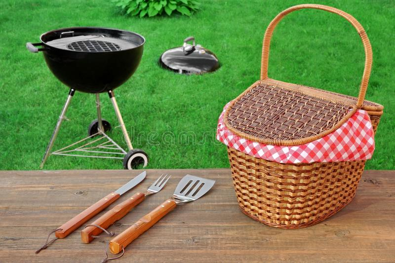Weekend Summer Outdoor BBQ Party Ot Picnic Scene. Weekend Summer Outdoor BBQ Grill Party Ot Picnic Conceptual Scene With Picnic Wood Table, BBQ Tools, Hamper And royalty free stock images