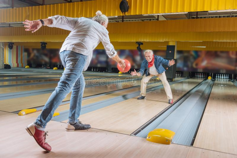Delighted nice elderly men having fun together. At the weekends. Delighted nice men having fun together while meeting in the bowling club royalty free stock photography