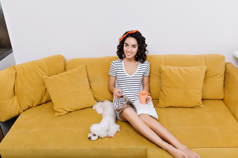 Weekends, free time of amazing pretty young woman with brunette cut curly hair smiling on orange couch in living room royalty free stock photo