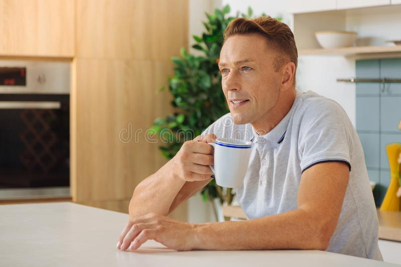 Positive handsome man resting at home royalty free stock photography