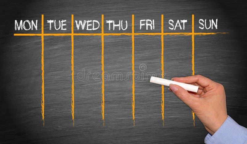 Weekly Calendar - female hand with chalk writing on blackboard royalty free stock photo