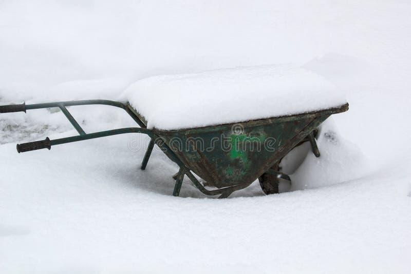 Weelbarrow resistido velho com neve no fundo branco da neve foto de stock