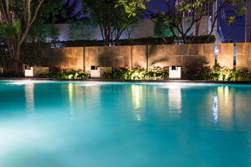 Weelderige poolverlichting in binnenplaats voor het ontwerp c van het luxe zwembad stock afbeelding