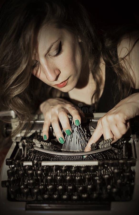 Weemoedige vrouw die een schrijfmachine herstelt royalty-vrije stock foto's