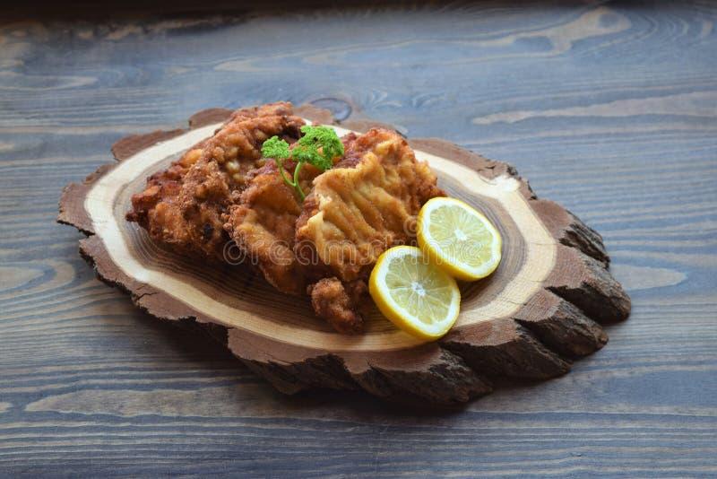 Weense schnitzel op een houten raad met citroen op een donkere achtergrond Vleesschotel stock afbeeldingen