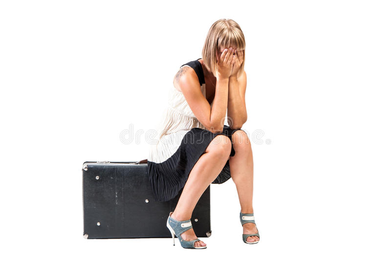 Weeping girl sitting on trunk - isolated. Young girl sit in big trunk and weep, isolated stock image