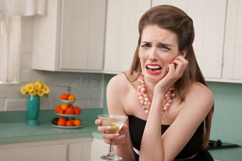 Weeping Woman with a Martini. Caucasian woman with a martini in her kitchen sobs royalty free stock photos