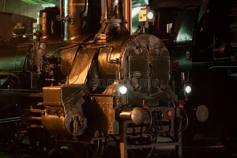 Weergave van een historische stoomlocomotief in een depot verlicht 's nachts royalty-vrije stock foto's