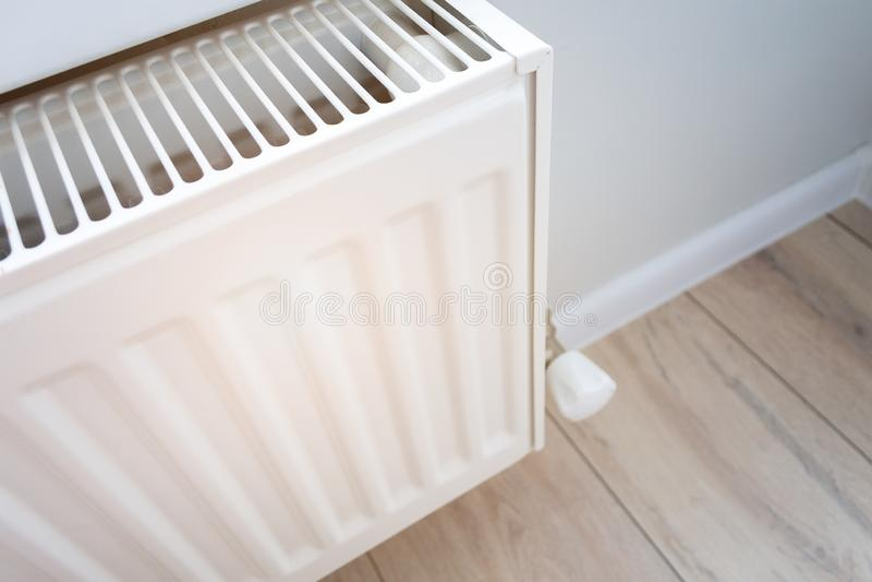 Weergave van een verwarmingsradiator voor thuisgebruik in een woonkamer met houten vloer en lichtwand stock foto