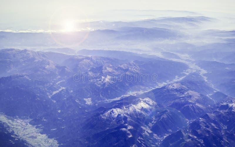 Weergave van het vliegtuig op de Alpen Adembenemend beeld van de ochtendgloren en de bergpieken in de sneeuw, paarse tinten en ho stock afbeelding