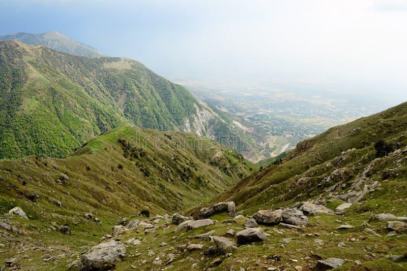 Weergeven aan de vallei van rotsachtige bergketen met groene weiden dichtbij Triund-Heuvel Heldere kleur India, de rand Himachala royalty-vrije stock afbeeldingen