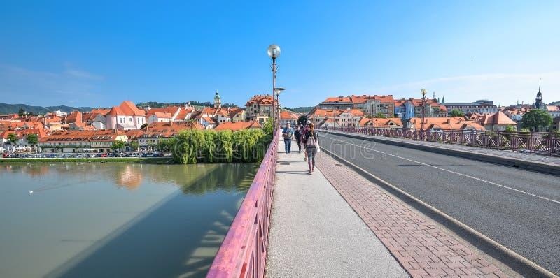 Weergeven op brug en voetgangers in Maribor-stadscentrum, Slovenië Dravarivier, gebouwen en bergen van Maribor stock fotografie