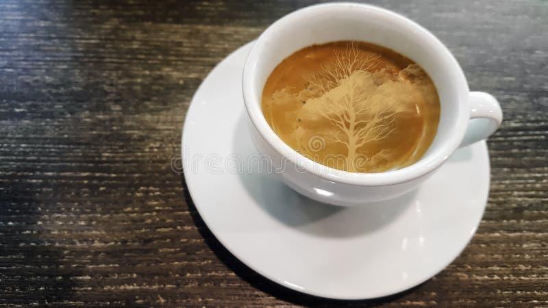 Weergeven op close-up, Ochtend met hete espresso in wit glas met rook Op een houten lijst aangaande een gevormde oppervlakte uits stock foto