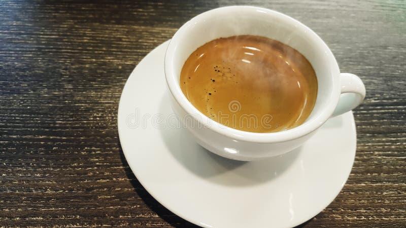 Weergeven op close-up, Ochtend met hete espresso in wit glas met rook Op een houten lijst bij een uitstekende toon van de patroon royalty-vrije stock foto's