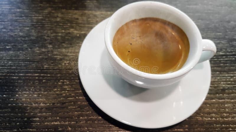 Weergeven op close-up, Ochtend met hete espresso in wit glas met rook Op een houten lijst bij een uitstekende toon van de patroon royalty-vrije stock afbeelding