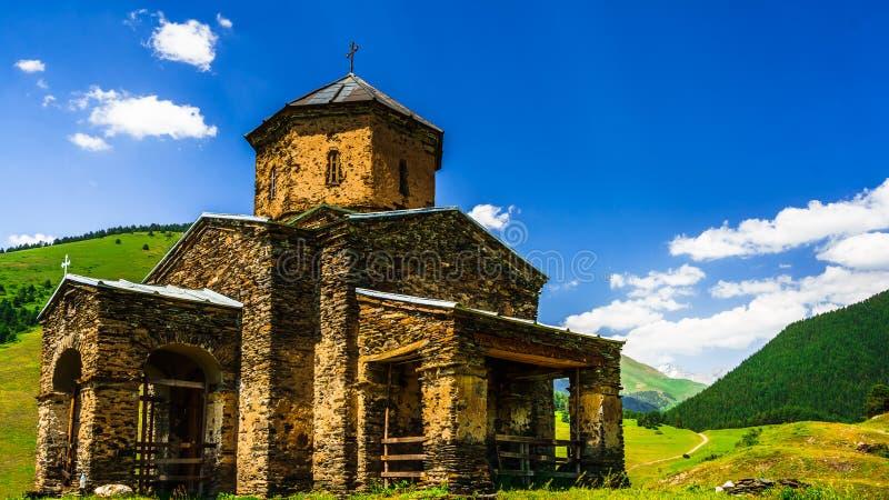 Weergeven op de Sameba-Kerk van de Heilige Drievuldigheid in het verre Tusheti-dorp van Shenako, Georgië stock afbeelding