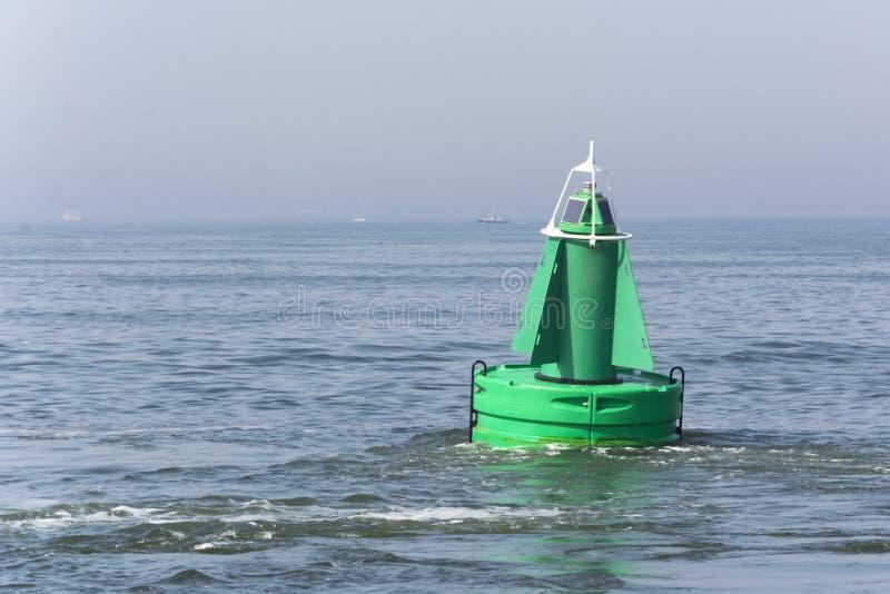 Weergeven op een groene boei in het overzees, een apparaat om schepen en boten te beschermen stock foto's