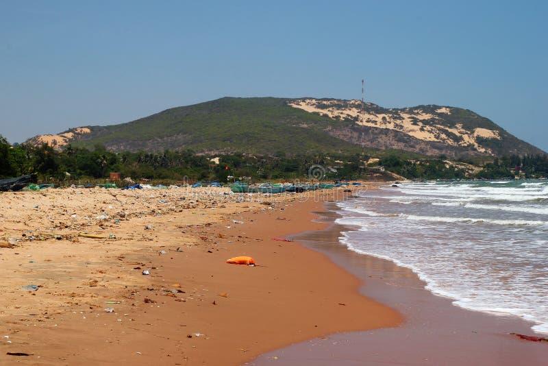 Weergeven op een verontreinigde kustlijn die dichtbij dorp met heel wat huisvuil vissen royalty-vrije stock foto's