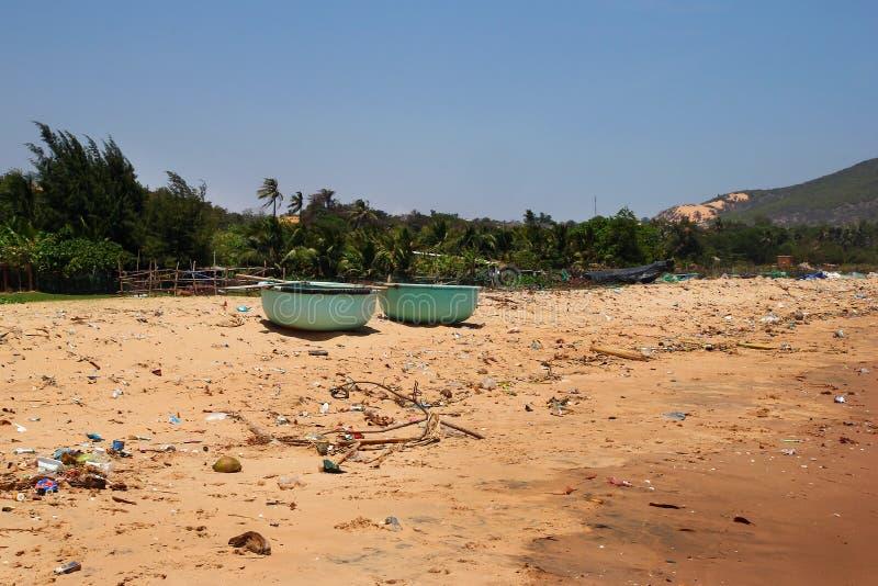 Weergeven op een verontreinigde kustlijn die dichtbij dorp met heel wat huisvuil vissen royalty-vrije stock fotografie